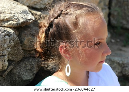 Adorable little girl in a green tunic in antique style on a background of ruins of the ancient city - stock photo