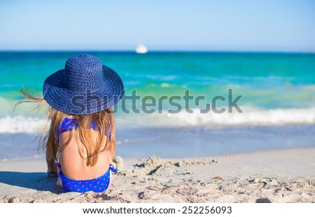 Adorable little girl in big blue straw hat at white beach - stock photo