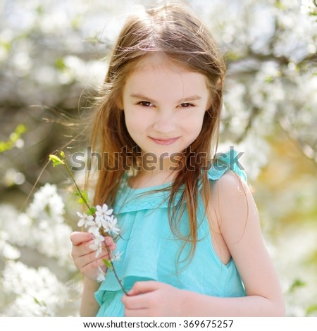 Adorable little girl in blooming cherry garden on beautiful spring day - stock photo