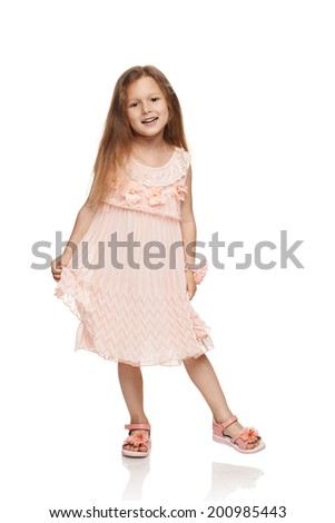 Adorable little girl in cream colored dress holding a hem of dress, in full length over white background - stock photo