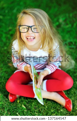 Adorable little girl in glasses holding book and laughing - outdoor portrait - stock photo