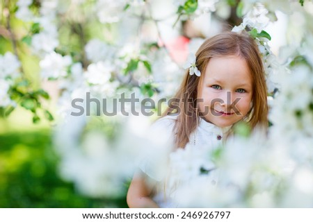 Adorable little girl in in blooming apple tree garden on spring day - stock photo