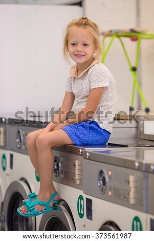 Adorable little girl in laundry room - stock photo