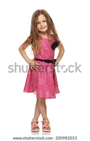 Adorable little girl in pink dress posing in full length over white background - stock photo