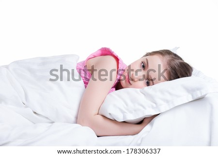 Adorable little girl in pink nightie awake in the bed on a white background. - stock photo