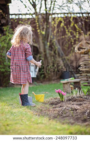 adorable little girl in plaid dress helps in garden with watering can in sunny spring day - stock photo