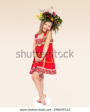 Adorable little girl in red traditional dress, put on her head a wreath of flowers - stock photo
