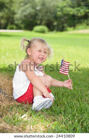Adorable little girl in red white and blue waving her flag outside - stock photo