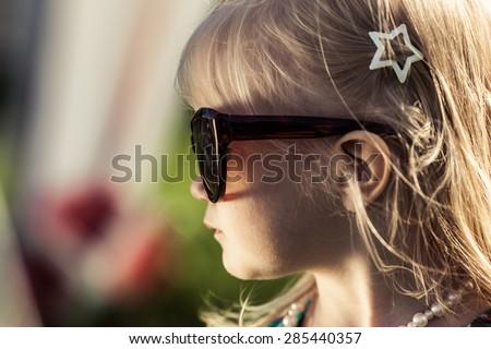 Adorable little girl in sun glasses. Bright sun. High contrast. Soft focus. - stock photo