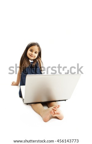 Adorable little girl is sitting on floor with her laptop. Isolated on white background  - stock photo