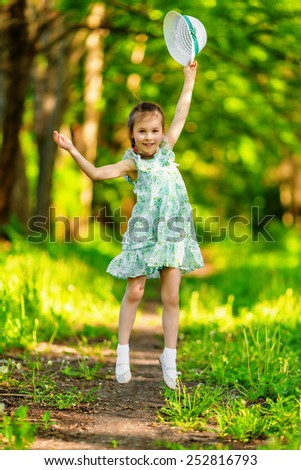 Adorable little girl jumping and having fun in summer day - stock photo