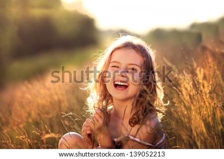 Adorable little girl laughing in a meadow - happy girl - stock photo
