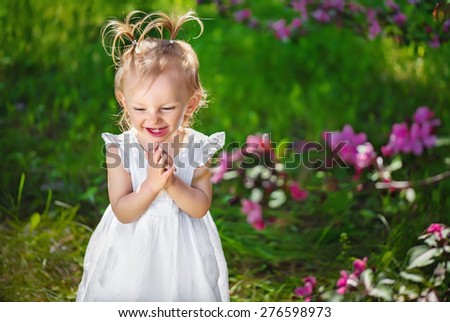 adorable little girl laughing, smiling and playing their hands in pat-a-cake in a park near a blossoming tree in the spring - stock photo