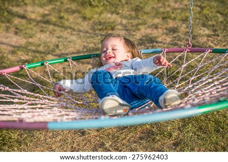 adorable little girl laying and smiling in a nest basket swing - stock photo