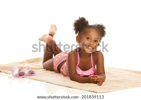 Adorable little girl laying out on a towel.  Isolated on white with room for your text. - stock photo