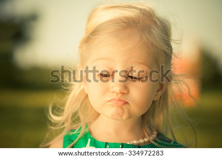 Adorable little girl making funny sad face. - stock photo