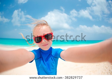 Adorable little girl making selfie at tropical white beach - stock photo