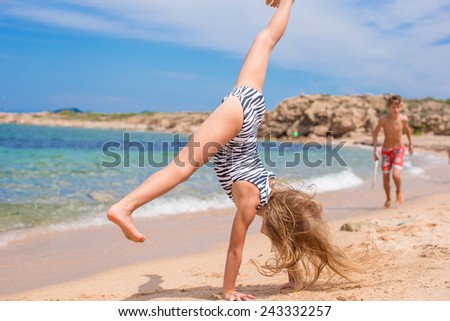 Adorable little girl making wheel on tropical white sandy beach - stock photo