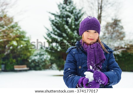 Adorable little girl of 8 years old playing in winter park, wearing warm blue coat, purple set of hat, scarf and gloves - stock photo