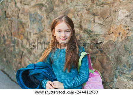 Adorable little girl of 7 years old ready to go to school, holding backpack and coat, wearing blue pullover - stock photo