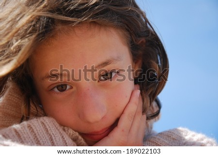 Adorable little girl on the beach in a cozy sweater - stock photo