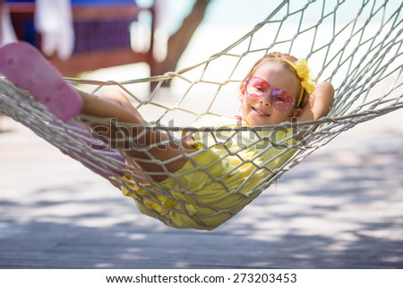 Adorable little girl on tropical vacation relaxing in hammock - stock photo
