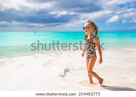 Adorable little girl on white beach during tropical vacation - stock photo