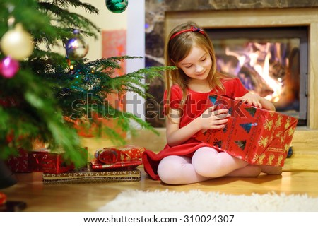 Adorable little girl opening Christmas gifts by a Christmas tree in cozy living room - stock photo