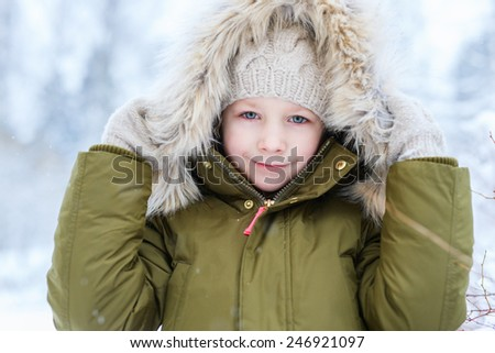 Adorable little girl outdoors on beautiful winter snow day - stock photo