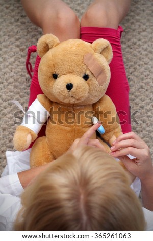 Adorable little girl playing doctor with her teddy bear - stock photo