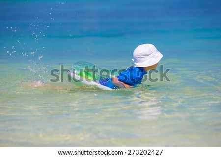 Adorable little girl playing in shallow water on white beach - stock photo