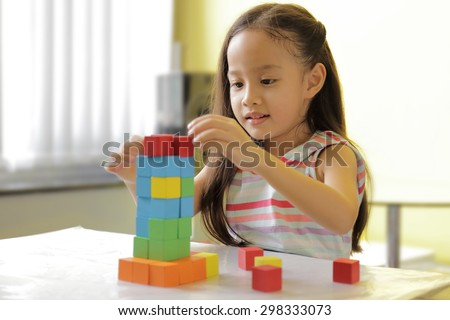 Adorable little girl playing toy blocks in a bright room - copy space on upper-left portion - stock photo