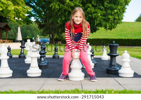 Adorable little girl playing with huge chess in a park on a nice day - stock photo