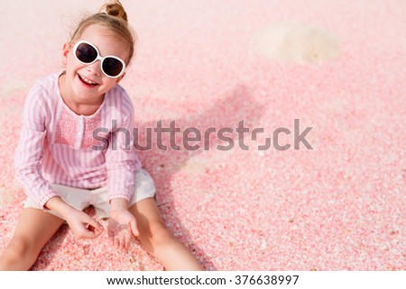 Adorable little girl playing with sand and shells on unique pink sand beach on Barbuda tropical island in Caribbean - stock photo