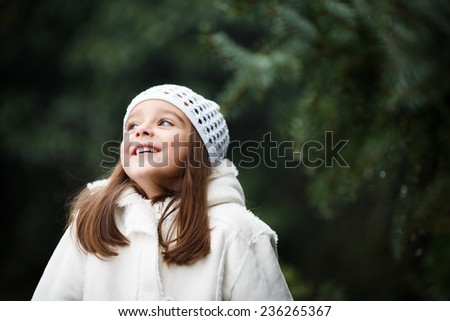 Adorable little girl posing near the branch of tree and smiling in to a camera. Wearing winter coat and hat. Lovely young girl in the winter outdoors. - stock photo