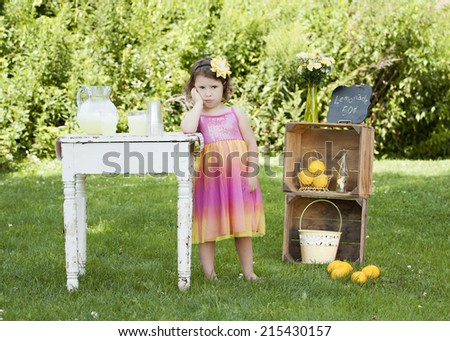 Adorable little girl pouting that she has no customers at her lemonade stand.   - stock photo