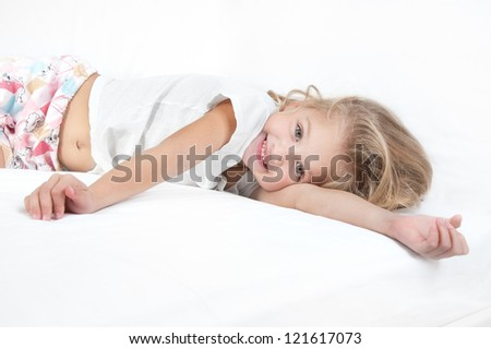 Adorable little girl resting in bed and looking at the camera close-up - stock photo