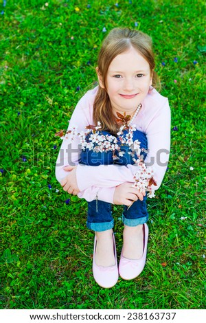 Adorable little girl resting outdoors on a nice sunny spring day, sitting on lawn, holding sakura brunch - stock photo