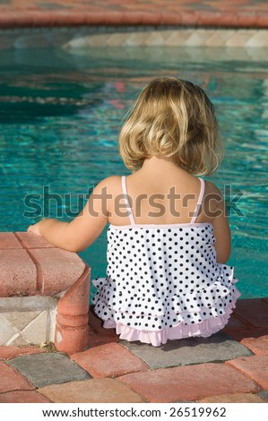 Adorable little girl sitting by pool - stock photo