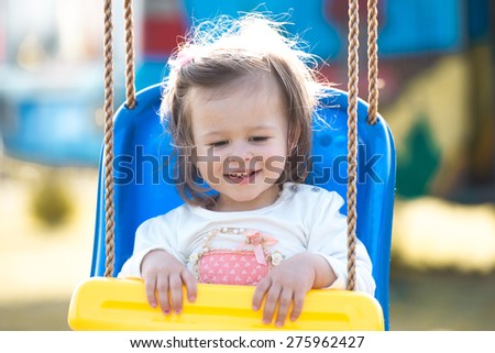 adorable little girl sitting in a swing laughing  - stock photo