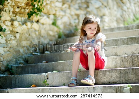 Adorable little girl sitting on stairs on warm and sunny summer day in typical italian town - stock photo