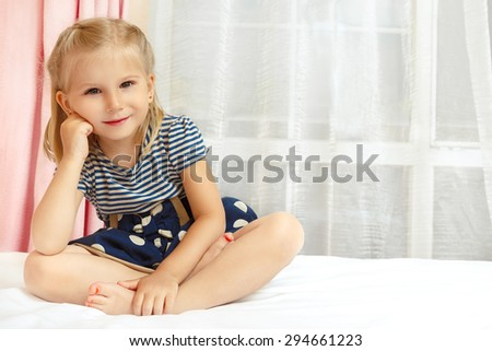 Adorable little girl sitting on the bed - stock photo