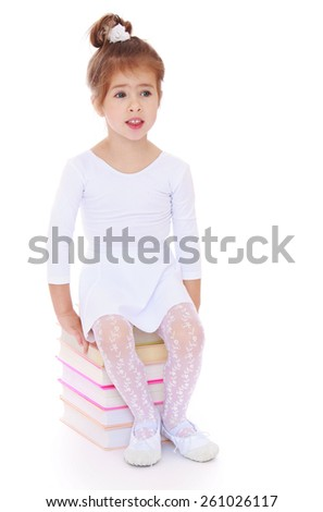Adorable little girl sitting on the books and dreams - isolated on white. - stock photo