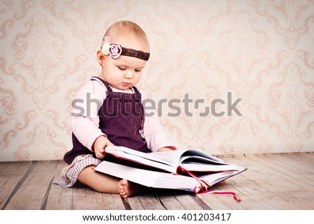 Adorable little girl sitting on the floor and holding big book - stock photo