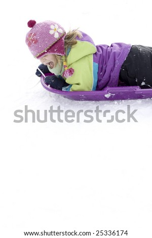 Adorable little girl sledding. - stock photo