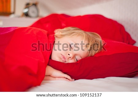 Adorable little girl sleeping in her bed - stock photo