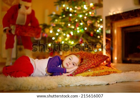 Adorable little girl sleeping under the Christmas tree by a fireplace on Christmas eve - stock photo
