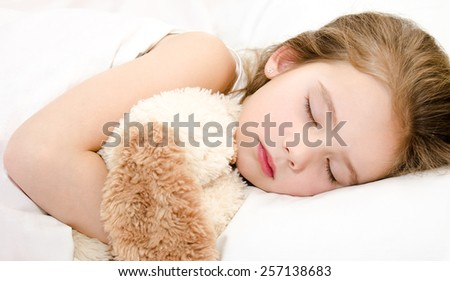 Adorable little girl sleeping with toy in her bed  - stock photo