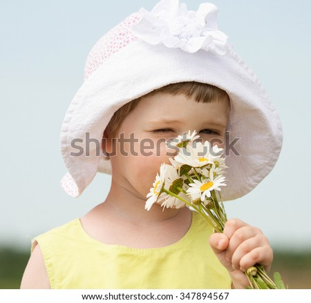 Adorable little girl smelling bunch of summer flowers - stock photo