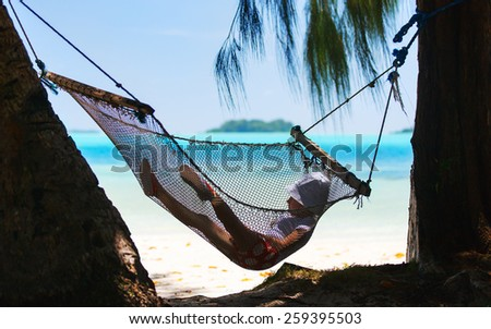 Adorable little girl swinging in hammock at beach - stock photo